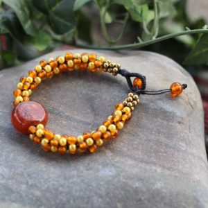 Orange and Yellow glass bead bracelet with a center Orange glass pendant. Made with cotton cord and a button bead clasp. Adjustable 7.5-8.5""