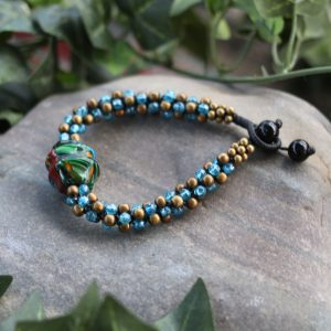 Blue crystal and metal bead bracelet with a center Mixed color glass pendant. Made on cotton cord with a button bead clasp. Adjustable 7.5-8.5""